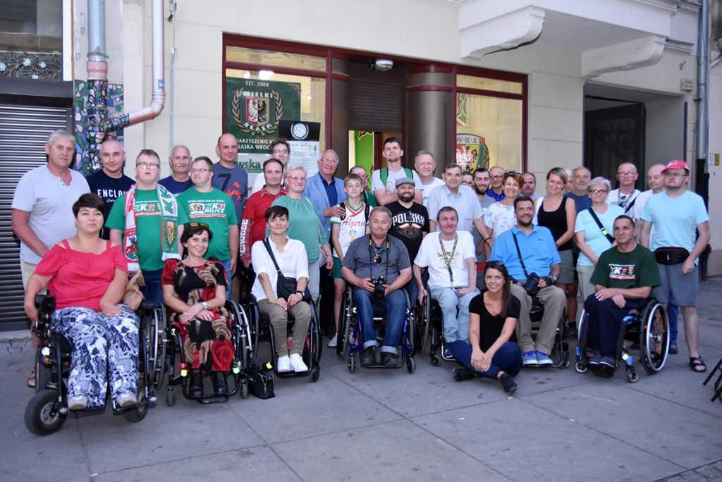 Grupa osób niepełnosprawnych i sprawnych przed siedzibą Kibice razem na Szewskiej