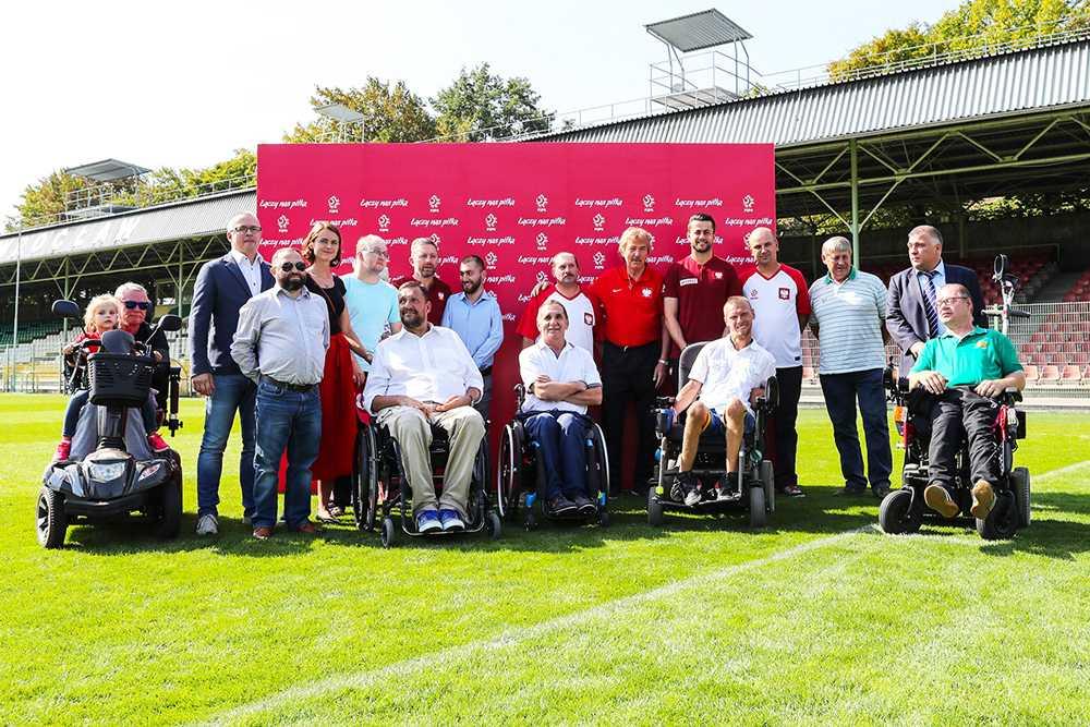 Na murawie ścianka PZPN, przed ścianką stoją włodarze PZPN, piłkarze i osoby niepełnosprawne
