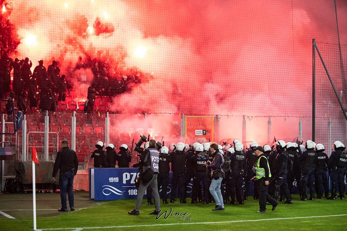 Na zdjęciu policja zgromadziła się pod sektorem kibiców WKS Ślaska Wrocław, którzy odpalili race. Policja próbuje opanowac sytuację z racami. Wszystko w czerwonym dymie z rac.