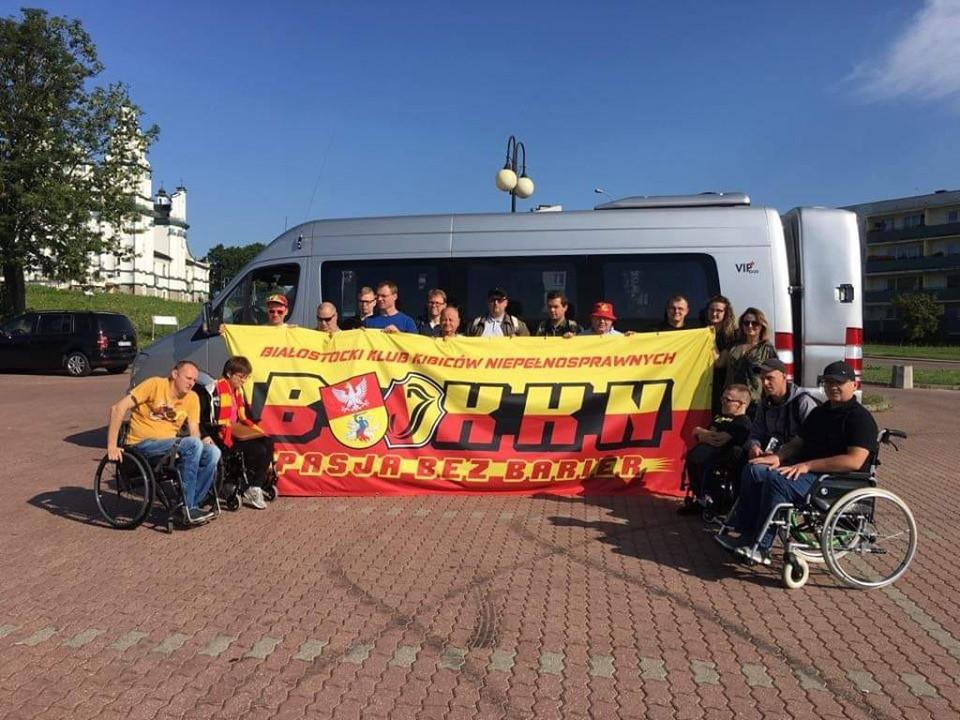 Kibice niepełnosprawni z Białegostoku wraz ze swoją żółto czerwoną flagą BKKN, w tle ich bus.