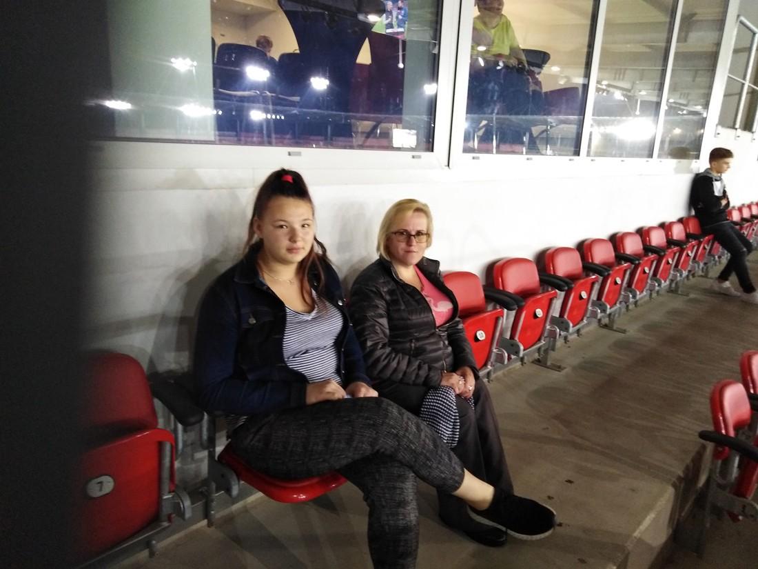 Zdjęcie przestawia dwie młode kobiety siedzące na trybunie stadionu. Kobieta z lewej strony jest szatynką i włosy ma upięte w kucyk. Kobieta z prawej strony jest blondynką, włosy o długości do ramion ma rozpuszczone. Nosi okulary. Obie kobiety są ubrane w ciemne spodnie i kurtki. Za kobietami znajdują się loże.