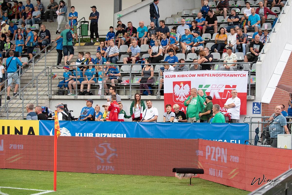 Trybuna wypełniona po brzegi kibicami. Na dole mocna grupa Wrocławskiego KNNu wraz z biało-czerwoną flagą wraz godłem Polski, obserwująca, rozmawiająca, kibicująca, uśmiechająca się i ciesząca z dobrego wyniku.