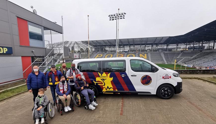 Niepełnosprawni kibice z opiekunami stoją przy busie