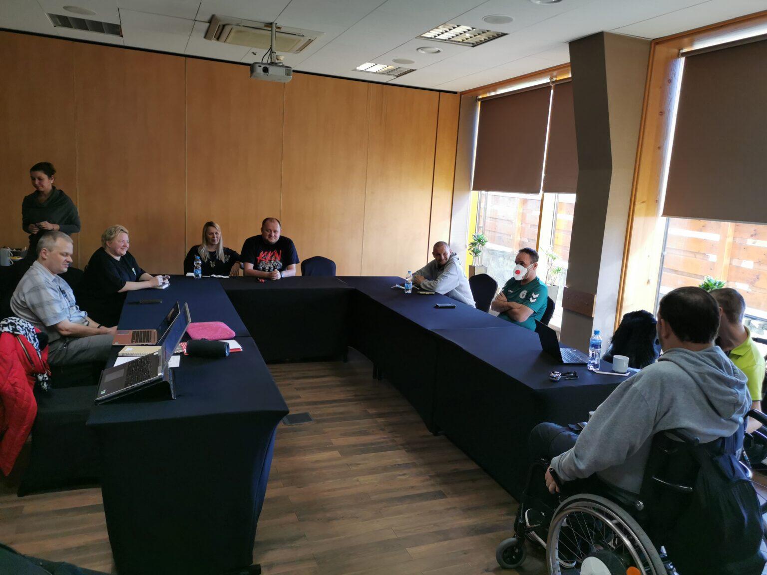 Sala konferencyjna, uczestnicy siedzą przy stołach ułożonych w literkę U.