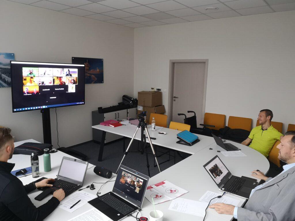 Sala konferencyjna, stoły ustawione w literkę U, na środku telewizor