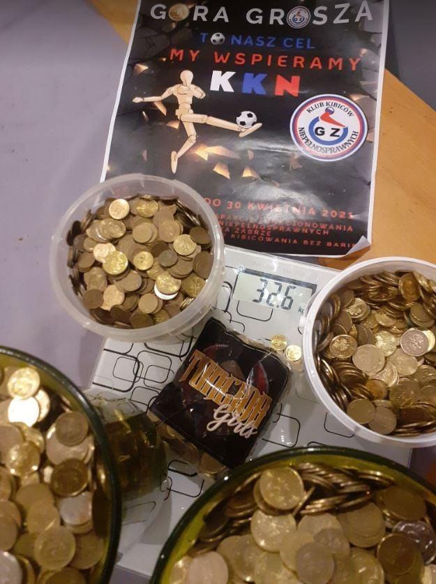 Na stole waga na której stoją 4 wiaderka z groszówkami, wynik na wadze wskazuje 32,6 kg