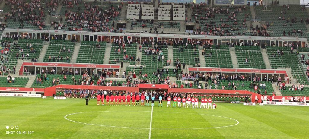 Piłkarze obu drużyn z sędziami stoją tyłem w jednym rzędzie na murawie przed rozpoczęciem meczu.
